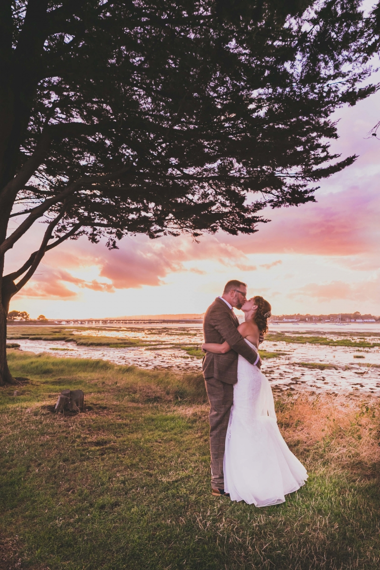 Newly weds kissing at sunset under a tree by Langstone Harbour