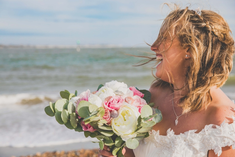 Happy bride smiling by the sea on Hayling Island